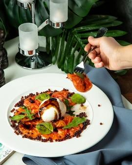 Вид сбоку человек ест салат каприз с рукколой и икрой