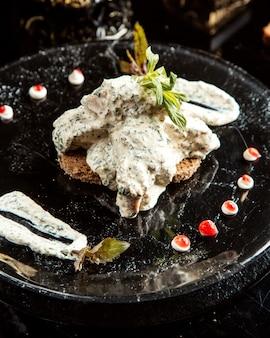 Вид сбоку мяса с соусом из греческого йогурта на тарелке