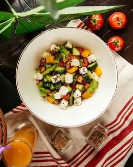 Вид сверху греческий салат с соком на столе