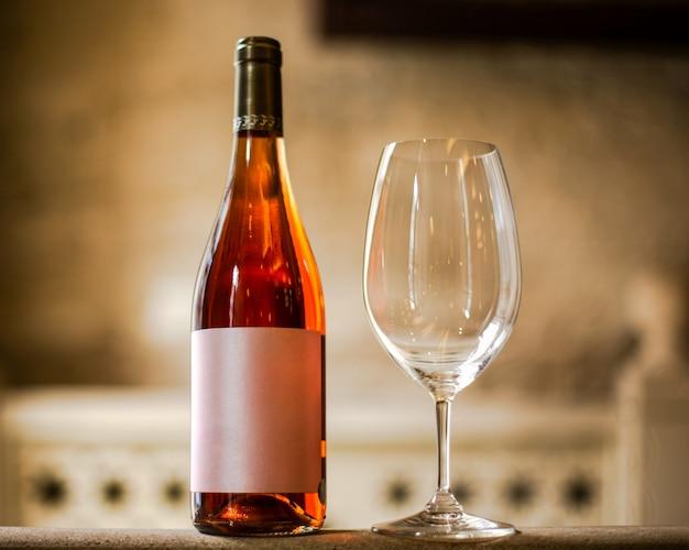 Вид спереди на бутылку вина и бокал на светлой стене