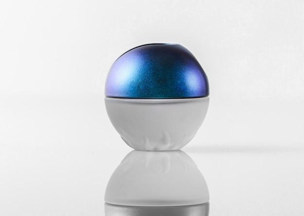 Вид спереди синяя белая бутылка, разработанная вокруг красивой на белой стене