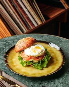 丸皿の上に卵と野菜が入った正面ハンバーガー