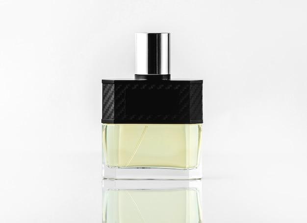 Вид спереди флакона аромата или парфюма в дизайнерских цветах на белой стене