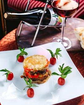 Вид спереди разработан блюдо цветной мясной муки украшен помидорами и зелеными листьями внутри белой тарелке