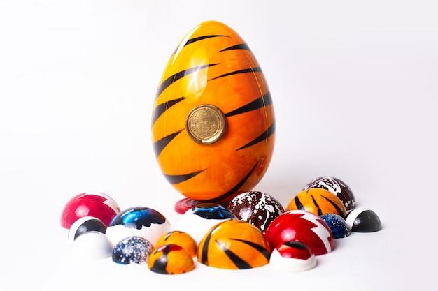 白い壁に描かれた正面の異なるチョコ卵とカラフルなキャンディー