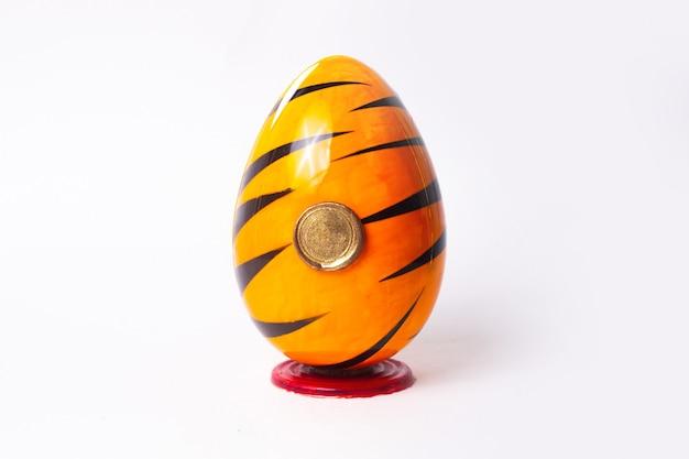 Вид спереди яйцо шоколадное оранжево-черное на белом столе