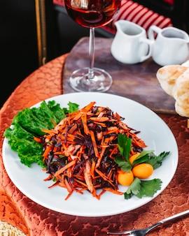 Вид спереди жареных овощей цветного витамина, богатый вместе с зеленым салатом внутри белой тарелке на столе