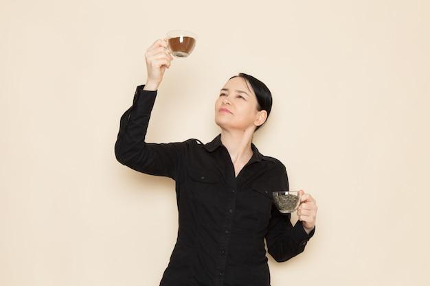 白い壁に乾燥した紅茶とコーヒーのカップを保持している黒いシャツのズボンの女性バリスタ