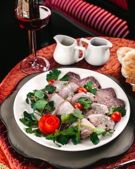 赤いチェリートマトと一緒においしい正面図シーフードとテーブルの上の白い皿の中の緑の葉