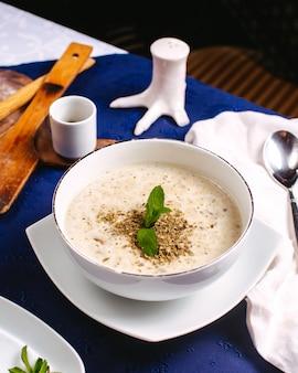 青い表面の白いお皿の中の緑の葉で飾られた正面スープ