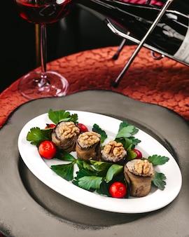 Вид спереди вкусная еда вкусный овощ вместе с красными помидорами черри и зелеными листьями внутри белой тарелке на столе