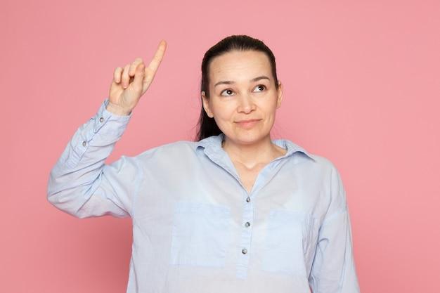 Молодая женщина в синей рубашке позирует на розовой стене