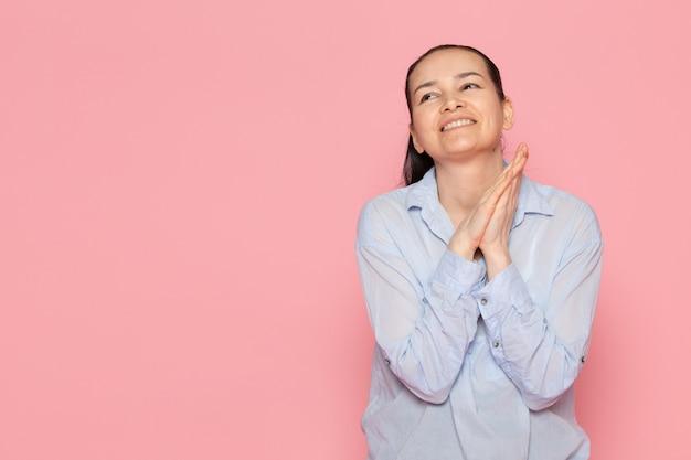 ピンクの壁でポーズ青いシャツの若い女性