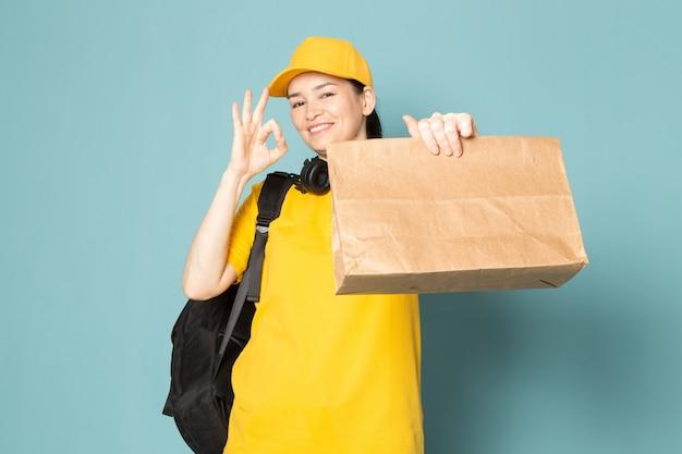 Молодая женщина-курьер в желтой футболке желтая кепка держит коробку на синей стене