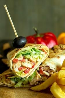 Крупным планом вид шаурмы бутерброд с куриным мясом капуста морковный соус зеленый, завернутый в лаваш