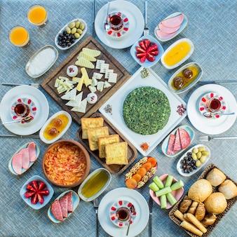 Вид сбоку на стол для завтрака с различными блюдами из жареных яиц с помидорами, колбасками, сыром, свежим салатом, десертом и чаем