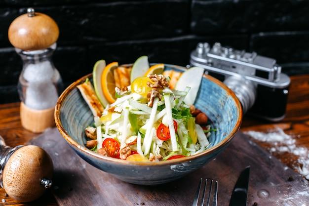 Вид сбоку салат цезарь с курицей и сыром пармезан в миску на темном