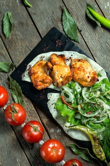 Вид сбоку куриного шашлыка, подается с луком, зеленью, жареными помидорами и перцем на черной доске