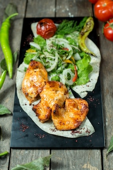 Вид сбоку куриного шашлыка, подается с луком на гриле помидор и перец на черной доске