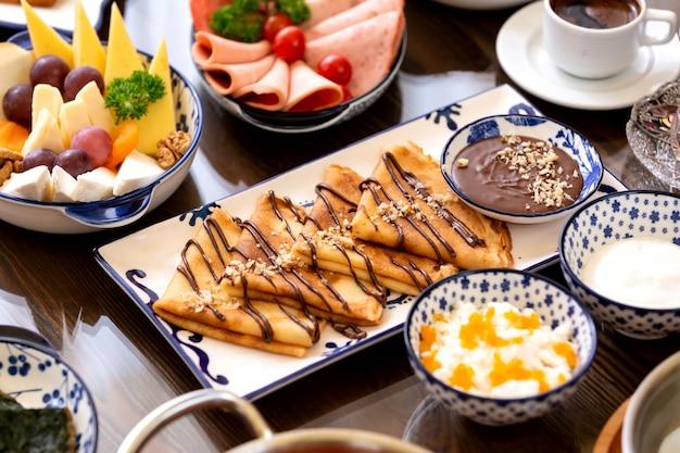 Вид сбоку блинов с шоколадным кремом и орехами на блюде