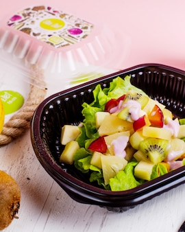 Вид сбоку фруктового салата с яблоками киви, ананасами и сливами, подается с йогуртом в коробке доставки
