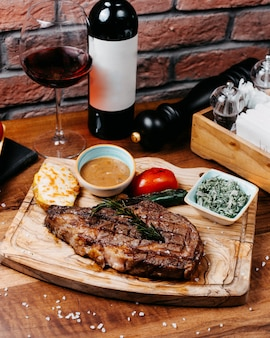 Вид сбоку гриль стейк из говядины с овощами и соусом на деревянной доске