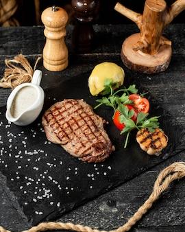 Вид сбоку на гриле стейк из говядины с овощами петрушкой и соусом на черной доске