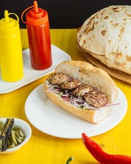 Мини-котлета на гриле с овощами и красным луком в хлебе, подается с соусами на столе, вид сбоку