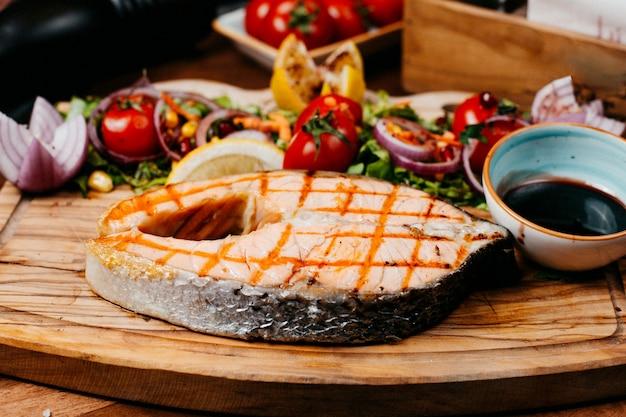 Вид сбоку жареного лосося с овощами и соусом на деревянной доске