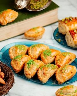 Вид сбоку восточного теста с орехами и фисташками на блюде