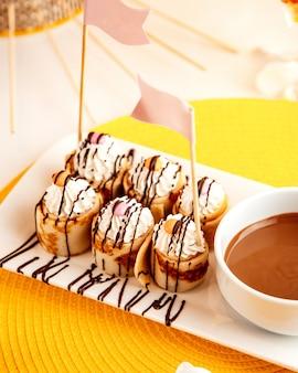 Вид сбоку блинчиков с взбитыми сливками и шоколадом на желтом