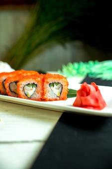 Вид сбоку суши-роллов с крабовым мясом, сливочным сыром и авокадо в икре летучей рыбы с соевым соусом на темном