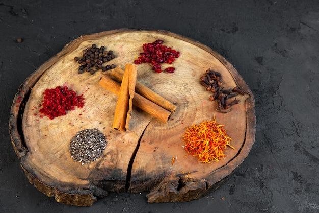 丸い木の板に様々なスパイスサフランチリパウダーブラックコショウとシナモンスティックの側面図