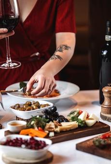 Вид сбоку сырной тарелки с виноградом и маринованными оливками