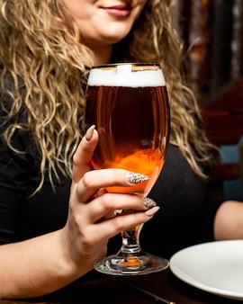 ビールのグラスを持つ女性の側面図