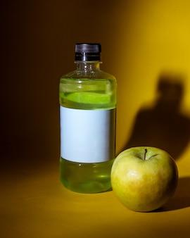 暗い黄色のテーブルの上のリンゴの瓶の中の緑のデトックスドリンクの側面図