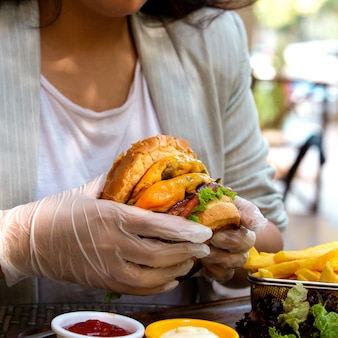 Вид сбоку руки, держащей бургер с говяжьей котлетой плавленым сыром и помидорами