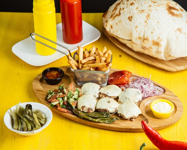 Вид сбоку мини-котлеты с плавленым сыром, рубленым овощным салатом, солеными огурцами и соусом из деревянных блюд