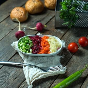 Вид сбоку смеси вареных овощей свекла морковь картофель подается с зеленым свежим нарезанным луком в белой миске