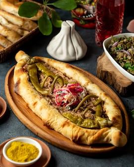 Вид сбоку традиционной грузинской кухни хачапури с мясом и маринованным острым зеленым перцем в деревянном блюде