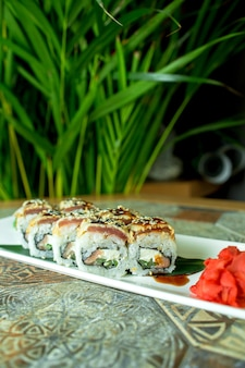Вид сбоку суши ролл традиционной японской кухни с авокадо угорь и сливочный сыр на зеленый