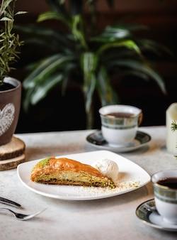 Вид сбоку турецкой сладости пахлавой треугольной формы с фисташками, подается с шариком мороженого на тарелке