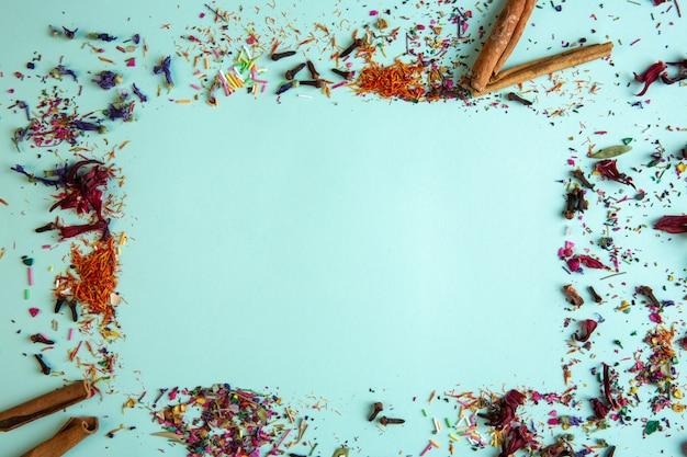 Вид сбоку различных специй с палочкой корицы и сухих цветочных лепестков с копией пространства на синем