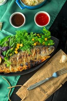 Топ запеченный сибас подается со свежей зеленью и соусами на столе