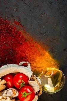 オリーブオイルのボトルと黒のトマトの束とトップのカラフルなスパイス