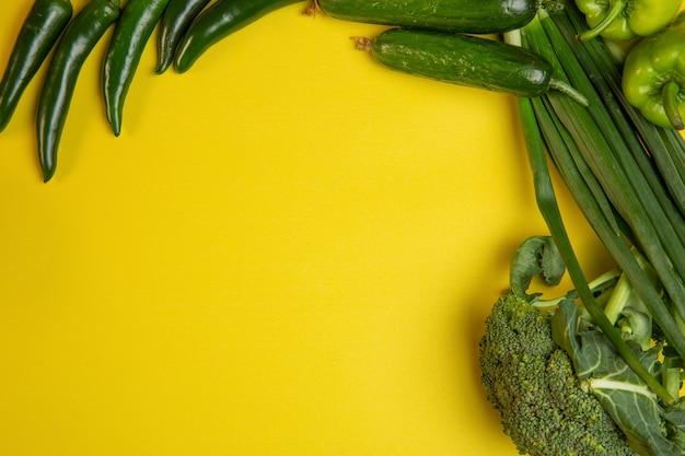 黄色の新鮮な野菜青唐辛子とキュウリのコピースペース平面図