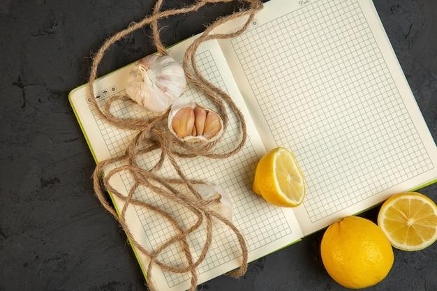 灰色の空のノートブックを開くにレモンスライスとニンニクの平面図