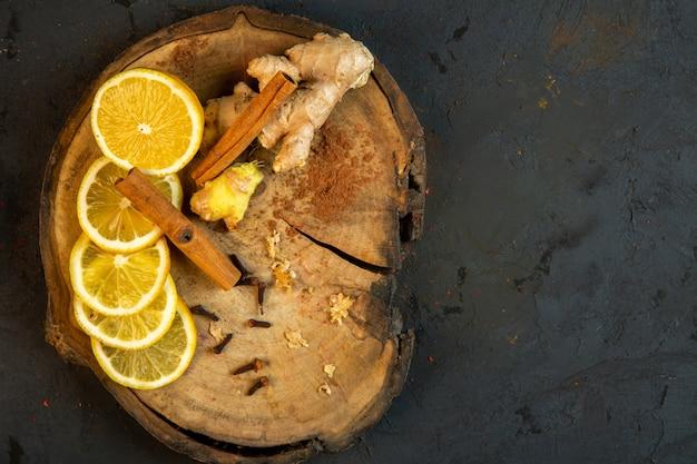 Вид сверху ломтики лимона палочки корицы и имбиря на деревянной доске на черном
