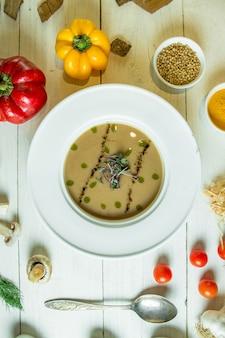 Вид сверху грибной крем-суп в миску белого