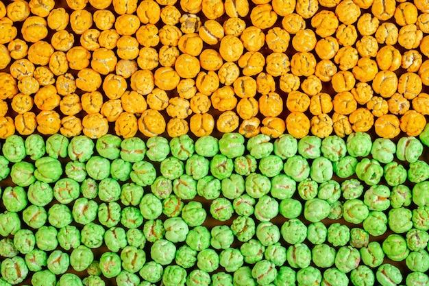 砂糖の背景で艶をかけられたナッツのトップビュー